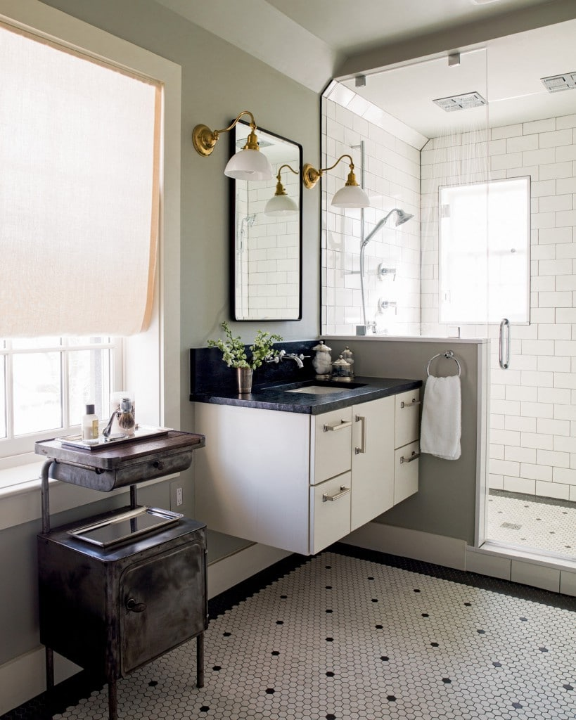 One of a pair of his-and-hers floating vanities in a master bath is shown here with vintage-style hex floors. White glass lamps beside the mirrors provide face-flattering light, and flush mount square rain shower heads lend a spa-like feel.
